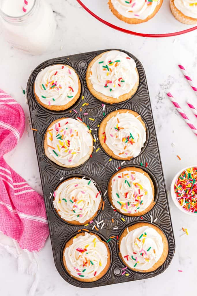 metal cupcake pan with frosted white cupcakes