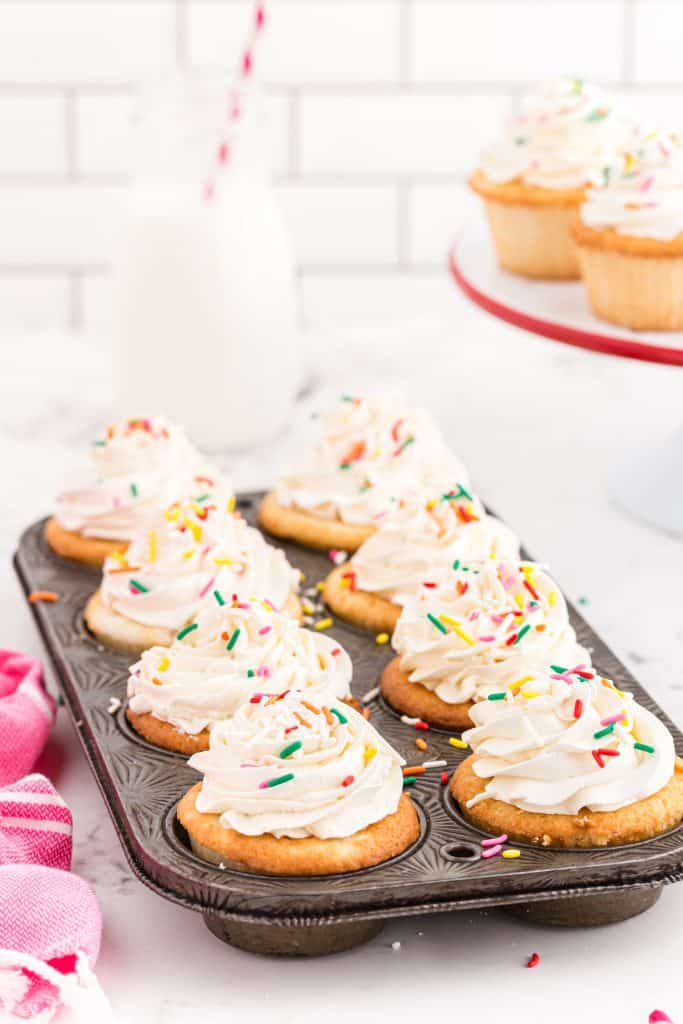 metal cupcake pan filled with frosted white cupcakes