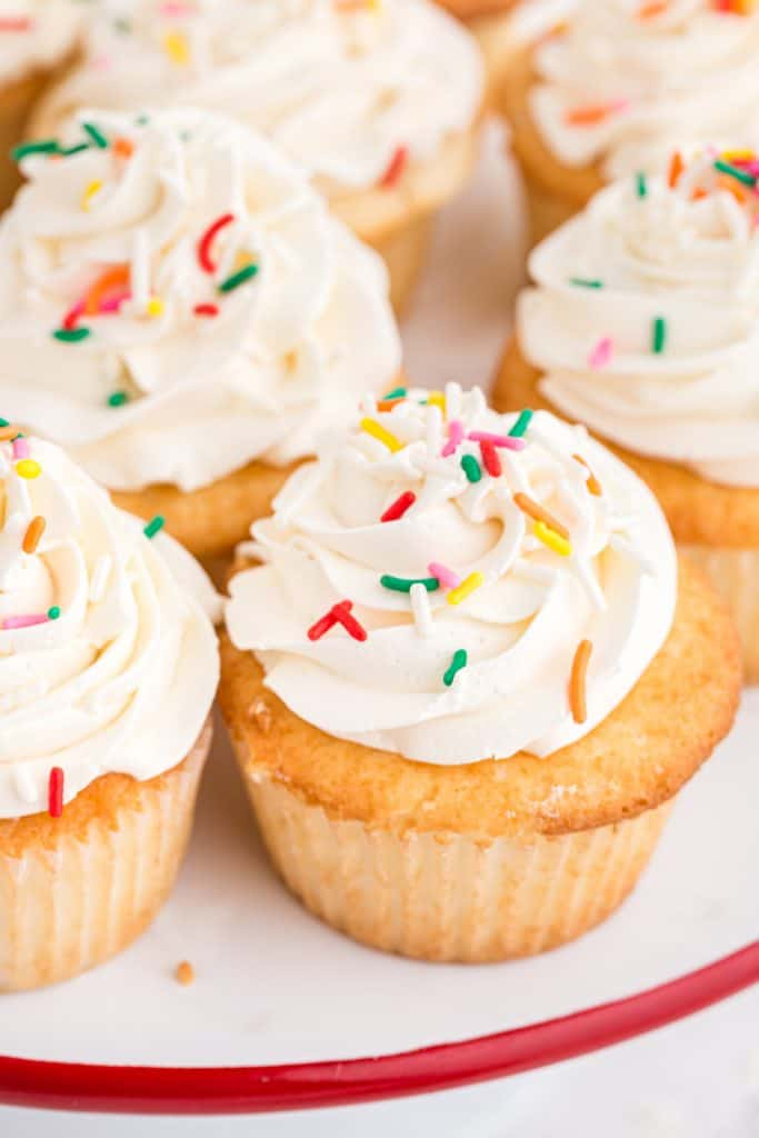 white cake plate with white frosted cupcakes