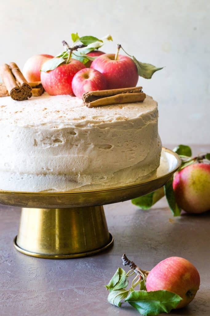 apple cider cake with fresh apples and cinnamon on gold cake stand