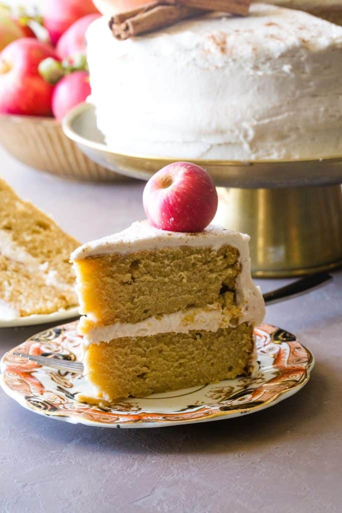 a slice of apple cider cake on plate with cake in the background