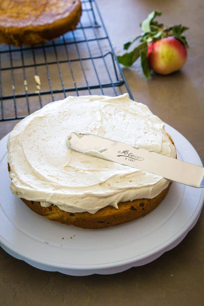 frosting the bottom layer of the apple cider layer cake