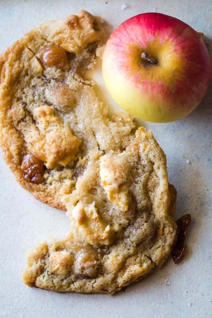 broken caramel apple cookie with whole apple next to it