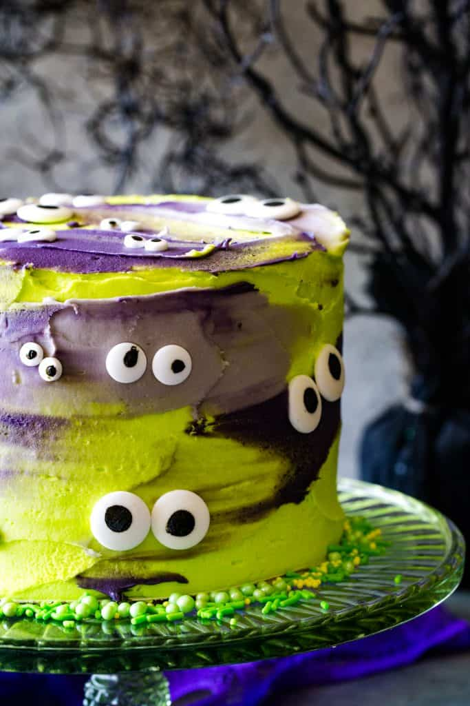 monster cake with candy eyes on green cake plate
