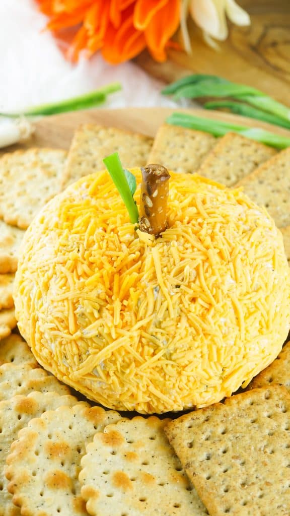whole pumpkin shaped cheeseball with crackers around