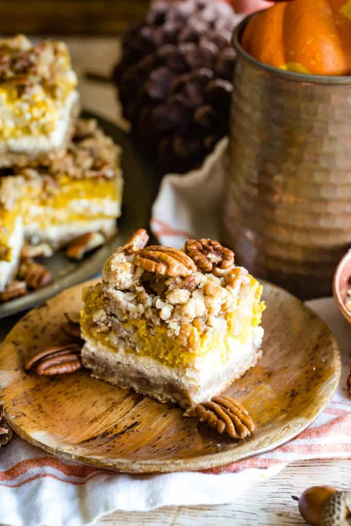 wood plate with pumpkin cream cheese bar and pecans