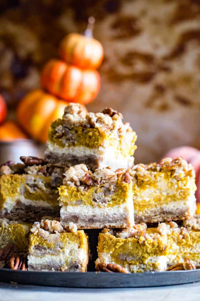 stack of pumpkin cream cheese bars with pumpkins in background