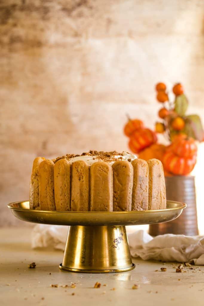pumpkin tiramisu on gold cake plate with beige background